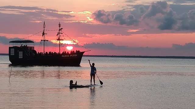 The Black Pearl and a paddleboarder at sunset. North Beach Haven